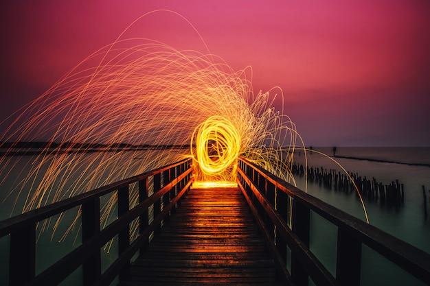 Mensen houden vuurwerk en draaien op lange bruggezichten op zee