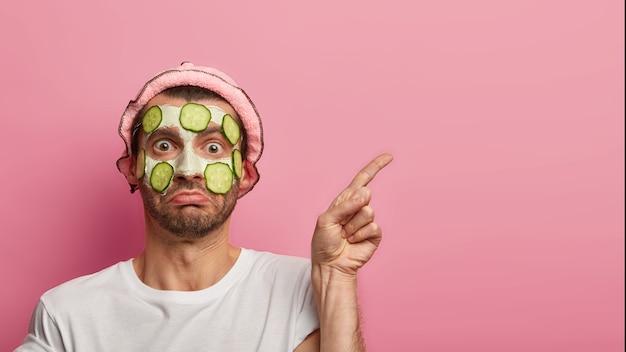 Mensen, huidverzorging en schoonheidsconcept. de verbaasde jongeman past gezichtsmasker met verse komkommers toe, wijst wijsvinger op lege ruimte