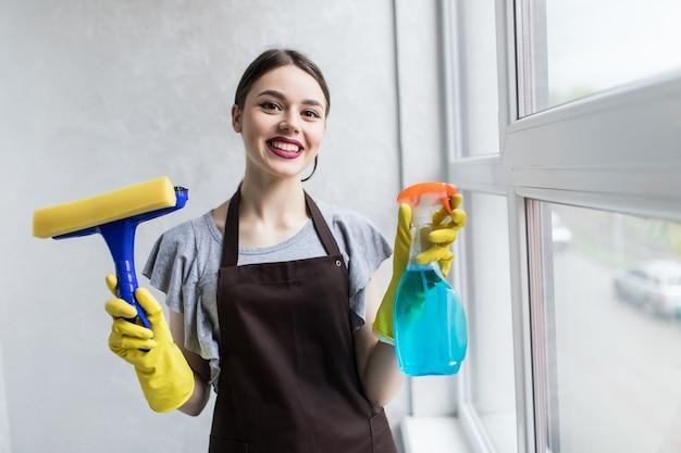 Mensen, huishoudelijk werk en huishoudelijk concept - gelukkige vrouw in handschoenen die het raam thuis schoonmaakt met vod en reinigingsspray