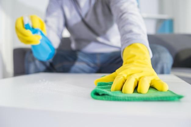 Mensen, huiswerk en huishouden concept - close-up van man handen schoonmaak tafel met doek en wasmiddel spuit thuis