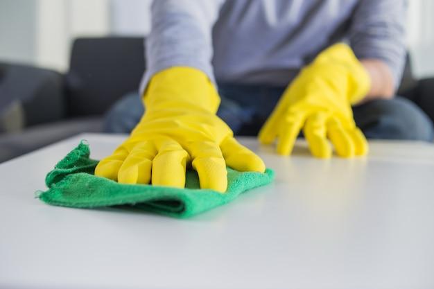 Mensen, huiswerk en huishouden concept - close-up van man handen schoonmaak tafel met doek thuis