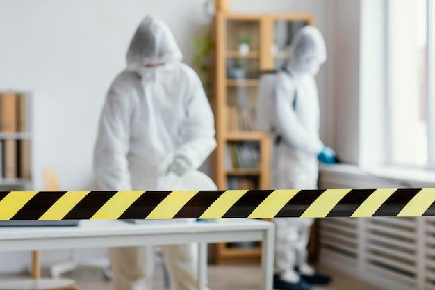 Mensen in beschermende uitrusting desinfecteren