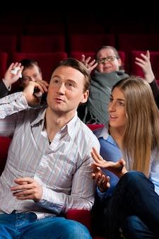 Mensen in bioscoop met mobiele telefoon