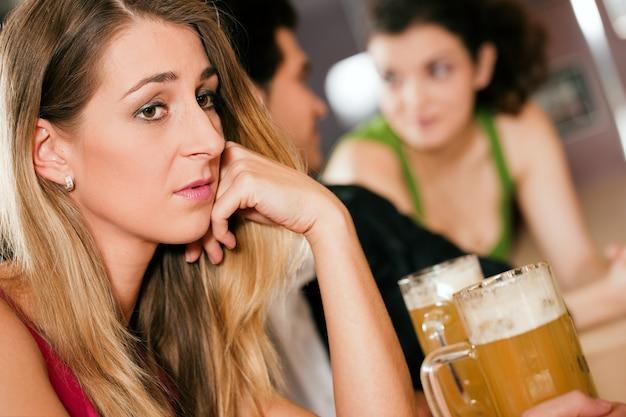 Mensen in de bar, vrouw verlaten en verdrietig
