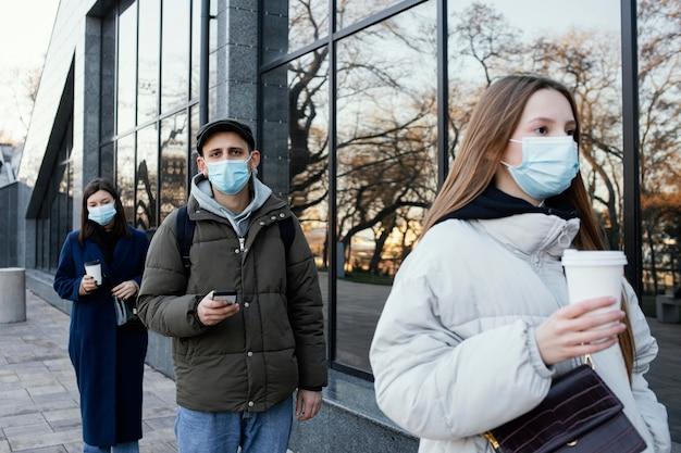 Mensen in de rij die maskers dragen