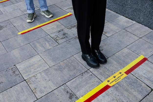 Mensen in de rij wachten achter sociale afstandsstreep