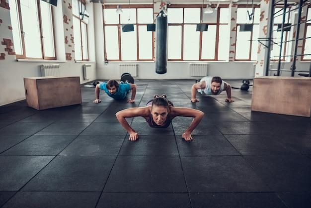 Mensen in de sportschool doen push-ups met trainer.