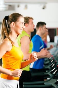 Mensen in de sportschool op loopband lopen