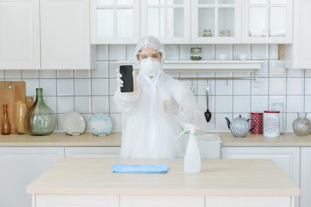 Mensen in een beschermend pak met desinfecterende huishoudelijke artikelen en meubels.