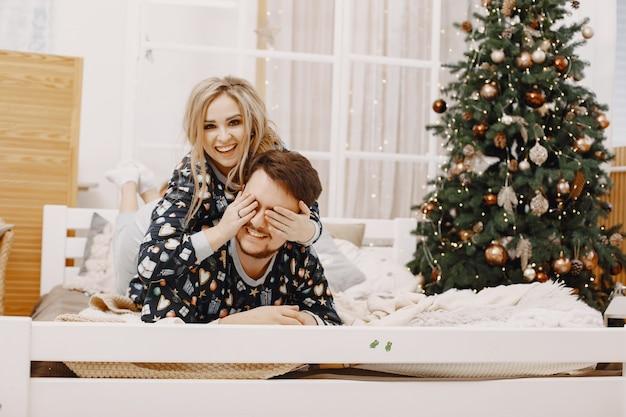 Mensen in een kerstversiering. man en vrouw in een identieke pyjama. familie op een bed.