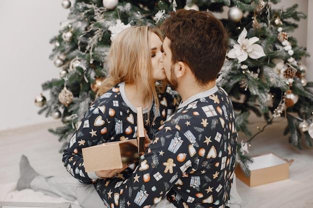 Mensen in een kerstversiering. man en vrouw in een identieke pyjama. familie thuis.
