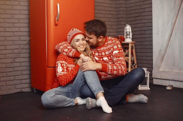 Mensen in een kerstversiering. man en vrouw in een rode trui.