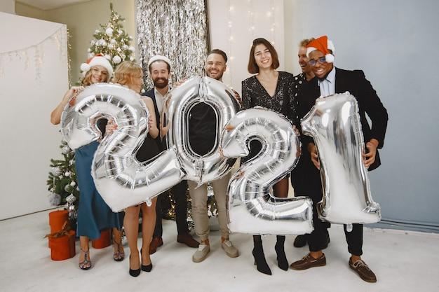 Mensen in een kerstversiering. man in een zwart pak. groepsvieringen nieuwjaar. mensen met ballons 2021.