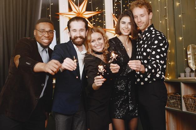 Mensen in een kerstversiering. man in een zwart pak. groepsvieringen nieuwjaar. mensen met bengaalse lichten.
