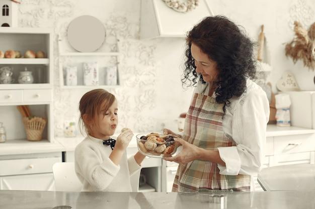 Mensen in een keuken. grootmoeder met dochtertje. de volwassen vrouw geeft meisjekoekjes.
