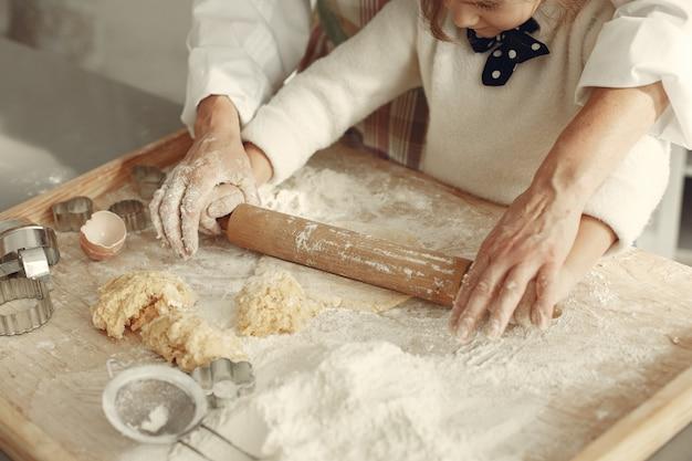 Mensen in een keuken. grootmoeder met dochtertje. volwassen vrouw leert meisje koken.