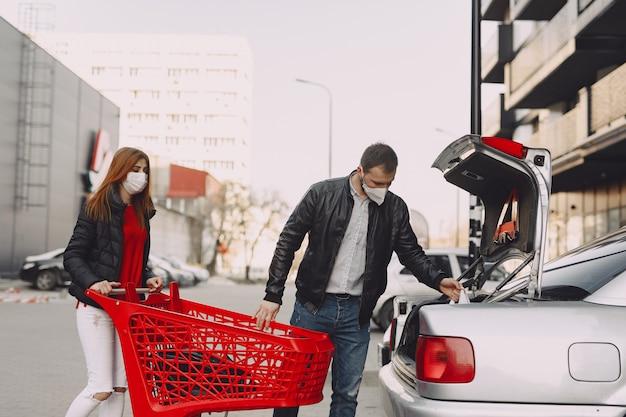 Mensen in een masker staan bij de kofferbak