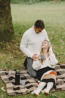 Mensen in een park. vrouw in een bruine jas. man in een witte trui. koppel in een picknick.