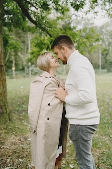 Mensen in een park. vrouw in een bruine jas. man in een witte trui.
