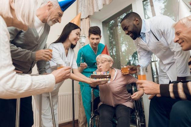 Mensen in een verpleeghuis feliciteren de vrouw met haar verjaardag.