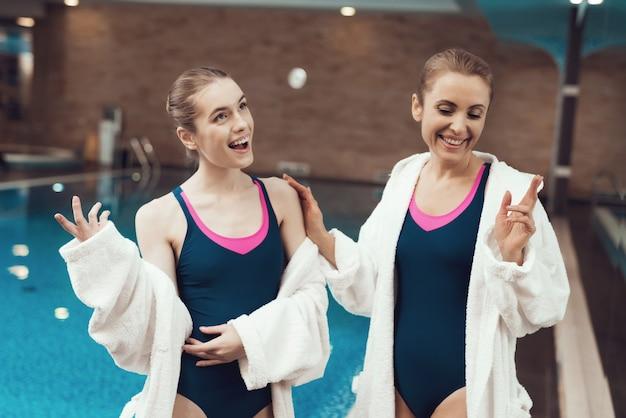 Mensen in gewaden en zwemkleding die bij het zwembad staan