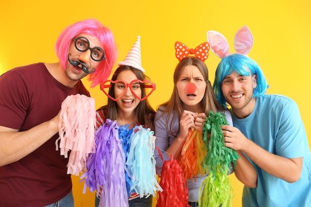 Mensen in grappige vermomming op kleurenachtergrond. viering van de dag van de dwazen van april