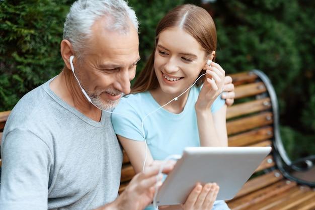 Mensen in het park en kijken naar iets op tablet.