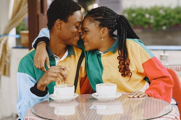 Mensen in identieke kleding. afrikaans paar in de herfststad. mensen aan tafel.