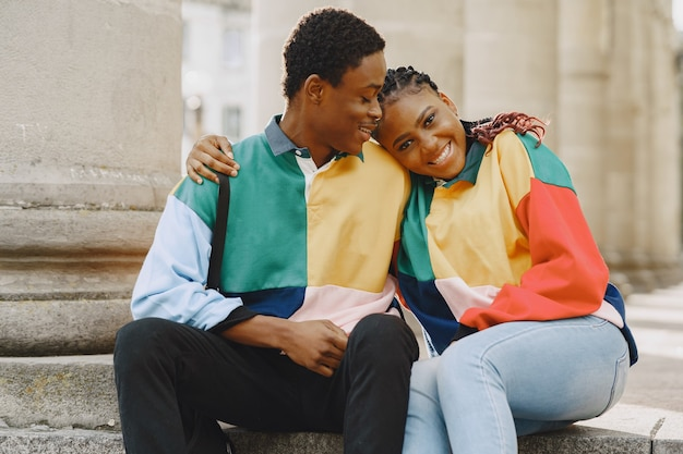 Mensen in identieke kleding. afrikaans paar in de herfststad. mensen die op straat zitten.
