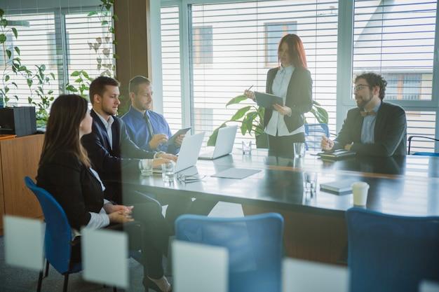 Mensen in kantoor luisteren naar presentatie