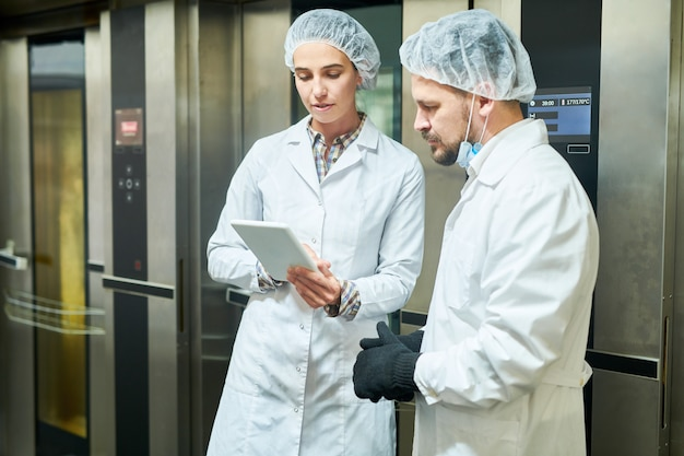 Mensen in laboratoriumjassen die en tablet bevinden zich gebruiken