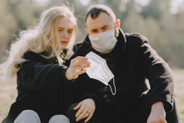 Mensen in maskers zitten in een bos
