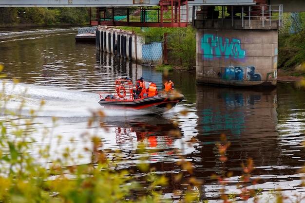 Mensen in reddingsvesten op motorboot drijvend op de rivier onder een ijzeren brug