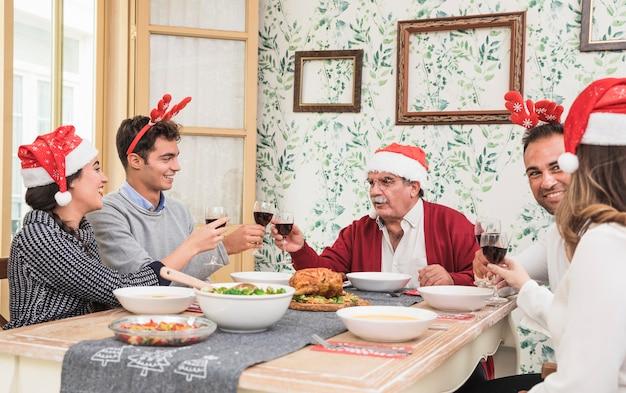 Mensen in santa hoeden rinkelen glazen aan feestelijke tafel