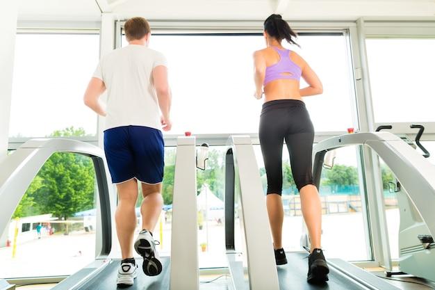 Mensen in sportgymnastiek bij lopende loopband