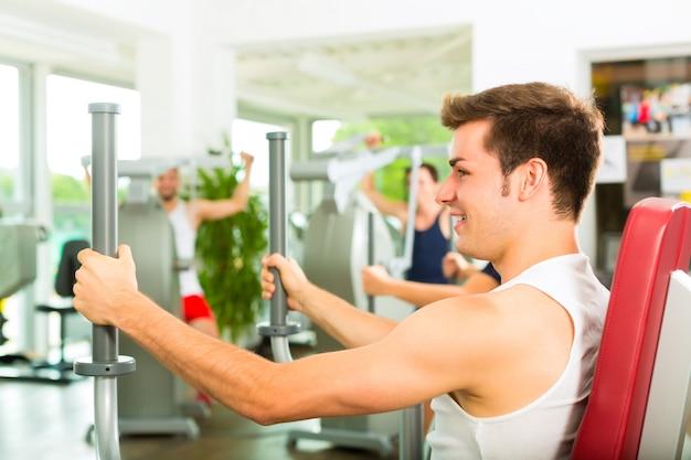 Mensen in sportgymnastiek op de fitnessmachine