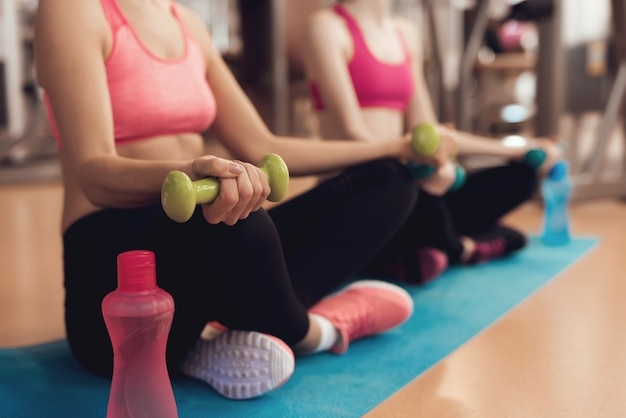 Mensen in sportkleding training met halters op sportschool