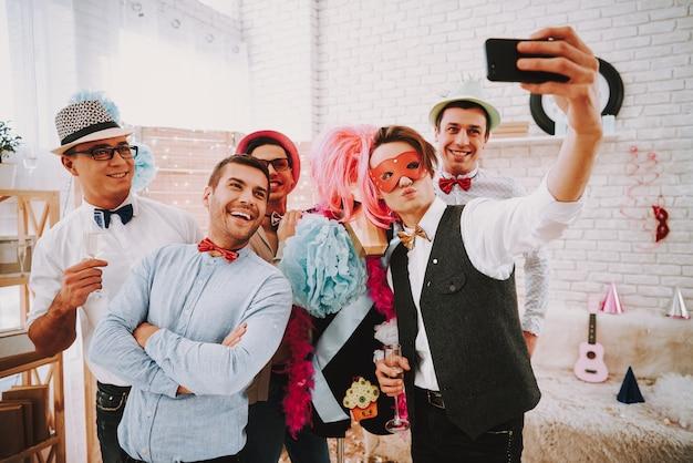 Mensen in strikjes selfie nemen op telefoon op feestje.