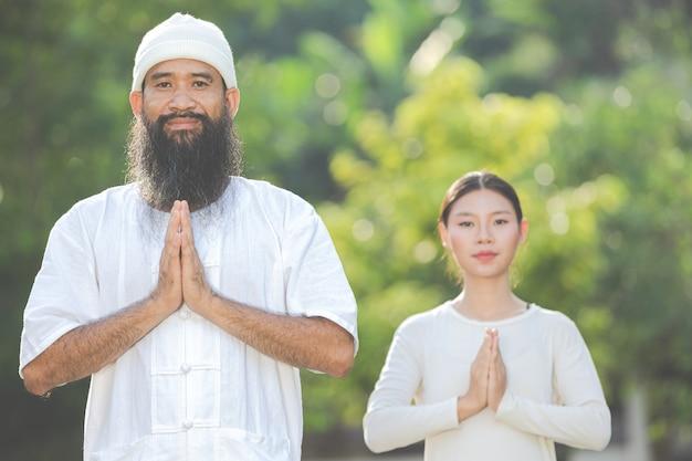 Mensen in witte kledij die hun eigen handen in een gebedspositie houden