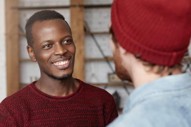 Mensen, interraciale vriendschap en communicatieconcept. knappe vrolijke jonge afro-amerikaanse man, gekleed in een gezellige trui die vrolijk verheugd glimlacht dat zijn blanke vriend is getrouwd