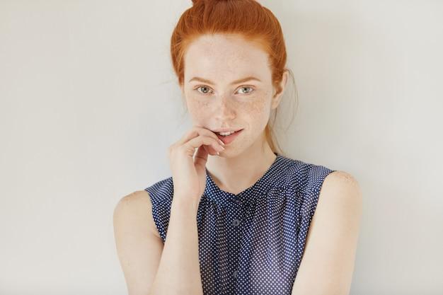 Mensen, jeugd en tederheid concept. portret van jonge roodharige vrouwelijke model dragen van mouwloos shirt met vlekken met verlegen schattige glimlach, hand op haar lippen houden en kijken, poseren binnenshuis