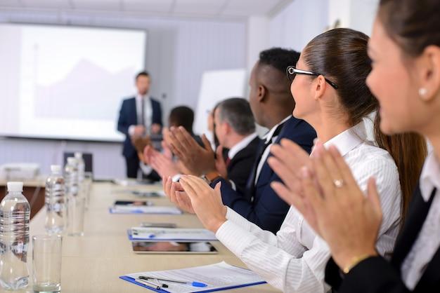 Mensen juichen de spreker toe tijdens een zakelijke bijeenkomst