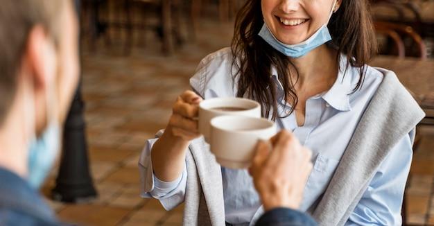 Mensen juichen met hun kopjes thee terwijl ze een gezichtsmasker op hun kin dragen