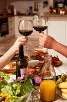 Mensen juichen met wijn aan tafel