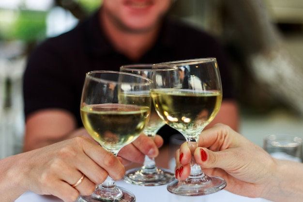 Mensen juichen met witte wijnglazen