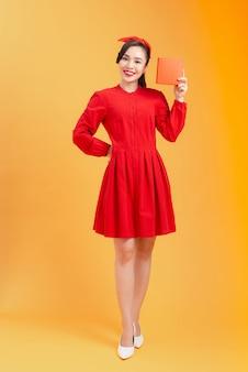 Mensen, kerstmis, verjaardag en feestdagen concept - gelukkige jonge vrouw in rode jurk tonen/houden met geschenkdoos over oranje achtergrond.
