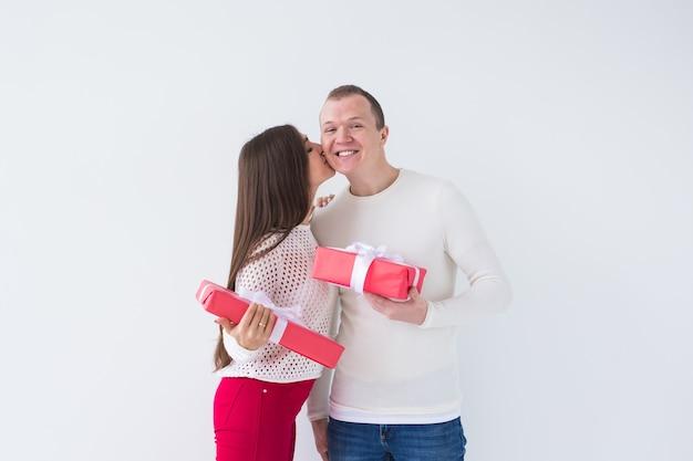 Mensen, kerstmis, verjaardag, feestdagen en valentijnsdag concept - gelukkige jonge man en vrouw met geschenkdozen op witte achtergrond met kopie ruimte.