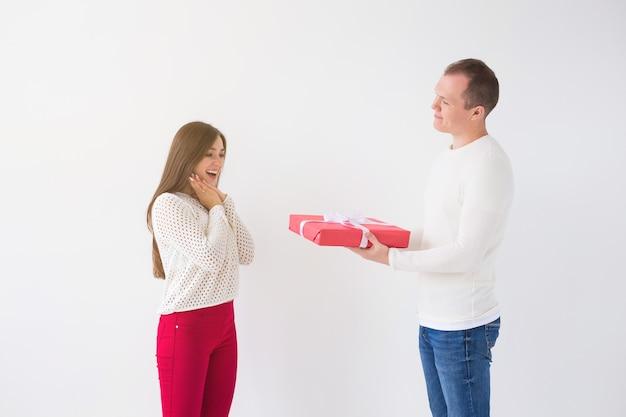 Mensen, kerstmis, verjaardag, feestdagen en valentijnsdag concept - knappe man geeft zijn vriendin een geschenkdoos op witte achtergrond.