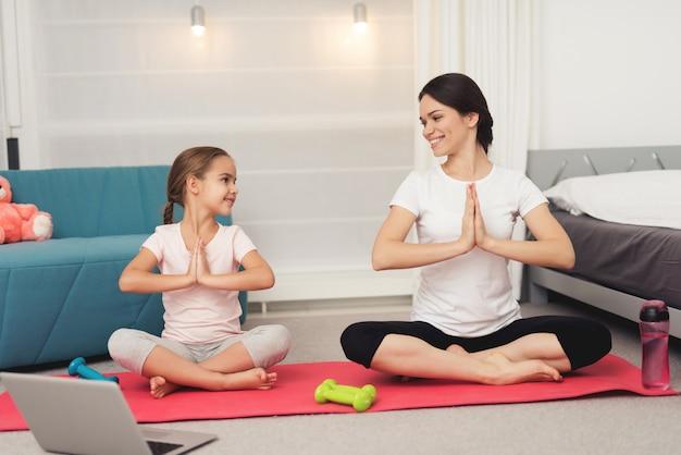 Mensen kijken naar de laptop op yogmat.