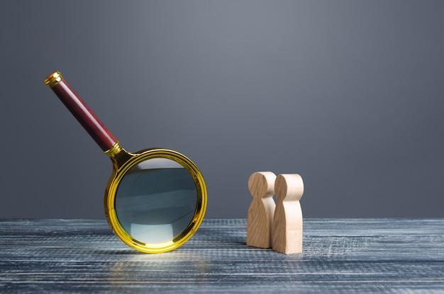 Mensen kijken naar een enorm vergrootglas. zoeken en analyseren, analyseren en bestuderen